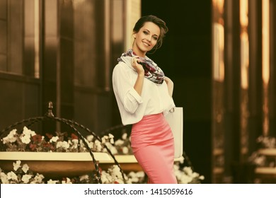 Young fashion business woman at office building Stylish female model in white shirt and pink pencil skirt