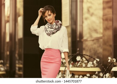 Young fashion business woman at office building on city street Stylish female model in white shirt and pink pencil skirt