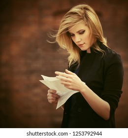 Young fashion business woman reading tax letter on city street Stylish female model in black suit jacket