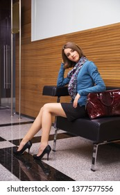 Young fashion business woman sitting on couch in office interior Stylish female model wearing blue cardigan and black pencil skirt