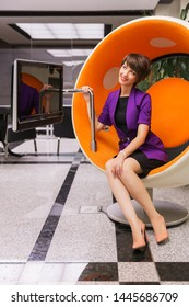 Young fashion business woman sitting on computer chair in office Stylish female model in purple blazer with pixie hair style