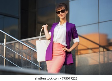 Young fashion business woman in sunglasses with handbag walking in city street Stylish female model in purple blazer and pink pencil skirt