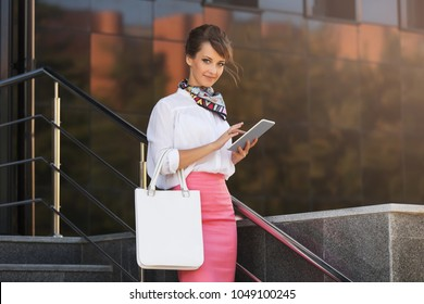 Young fashion business woman using digital tablet computer at office building. Stylish female model wearing white shirt and pink pencil skirt