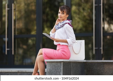 Young fashion business woman using digital tablet computer at office building Stylish female model in white shirt and pink pencil skirt