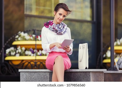 Young fashion business woman using digital tablet computer at office building Stylish female model in white shirt and pink pencil skirt outdoor