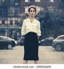 Young fashion business woman walking in city street Stylish female model wearing white shirt and black pencil skirt outdoor