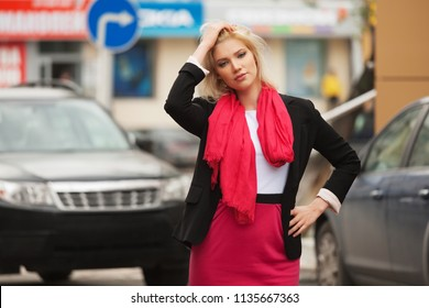 Young fashion business woman walking in city street Stylish female model wearing black suit jacket and red scarf outdoor