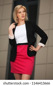 Young fashion business woman walking in city street Stylish female model wearing black suit jacket and pink skirt