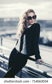 Young fashion business woman walking in city street. Stylish female model in sunglasses outdoor