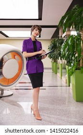 Young fashion business women with file folder at office Stylish female model in purple blazer and black pencil skirt