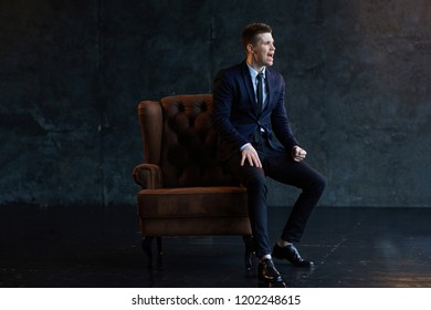Young fashion businessman sitting on the couch. Screaming. Rejoices victory. Emotions.