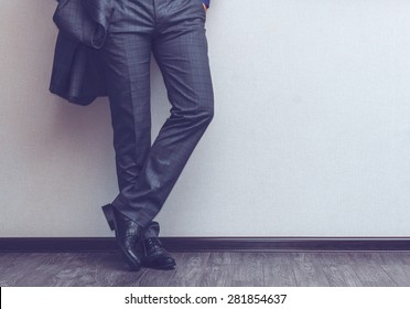 Young fashion businessman's legs in classic suit and shoes on wooden floor