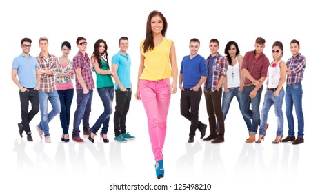 young fashion casual woman walking forward in front of a large team