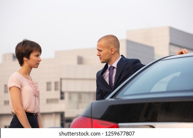 Young fashion couple in conflict talking beside a car on city street Stylish man wearing dark blue business suit and woman in pink blouse and black skirt
