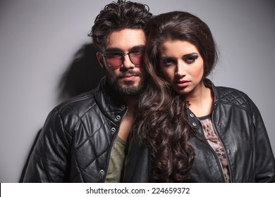 Young fashion couple posing against a grey wall, looking at the camera
