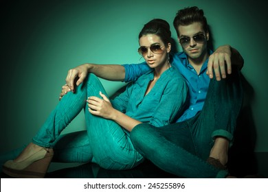 Young fashion couple sitting and leaning on a wall while looking at the camera.