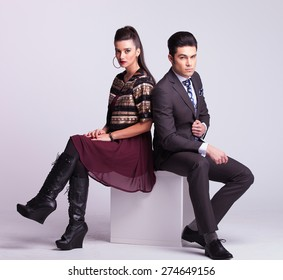 Young fashion couple sitting on a white table back to back.