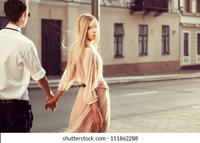 Young fashion couple walking down the street in summer in europe. Pretty beautiful woman looking in camera. Creamy sunlight