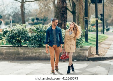 Young fashion couple walking down the street in summer in europe.