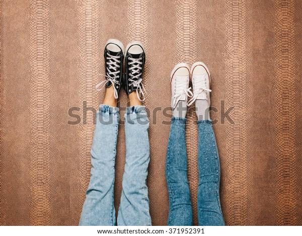 若いファッションカップルの足がジーンズで、スニーカーが壁に上がる
