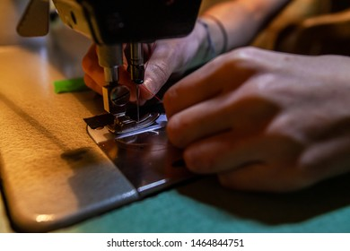 Young fashion designer changing thread. Hands of a young dressmaker are seen close up, replacing red thread on an industrial sewing machine. Awkward task before stitching fabric with machinery.