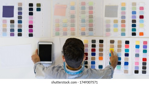 Young fashion designer choose the fabric color that will be used with the design on a table full of brightly colored fabric samples. Morning atmosphere in the tailor's shop. (Top View)