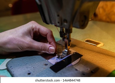 Young fashion designer on sewing machine. A closeup view on the hands of a young seamstress threading an industrial sewing machine in workshop, using red thread ready to create new garment.