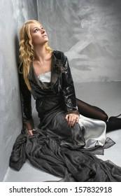 Young fashion designer sitting on the floor among fabrics