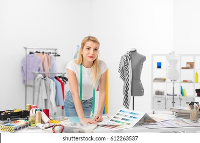 young fashion designer smiling and standing in front of the desk in the workshop