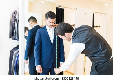 Young fashion designer taking measurement of man wearing elegant suit in tailor shop