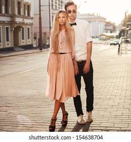 Young fashion elegant stylish couple posing on streets of european city in summer evening weather. Sensual blonde vogue girl with handsome hipster man having fun outdoor.