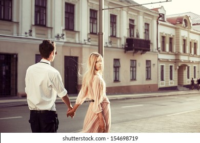 Young fashion elegant stylish couple posing on streets of european city in summer evening weather. Sensual blonde vogue girl with handsome hipster man walk on the road in europe