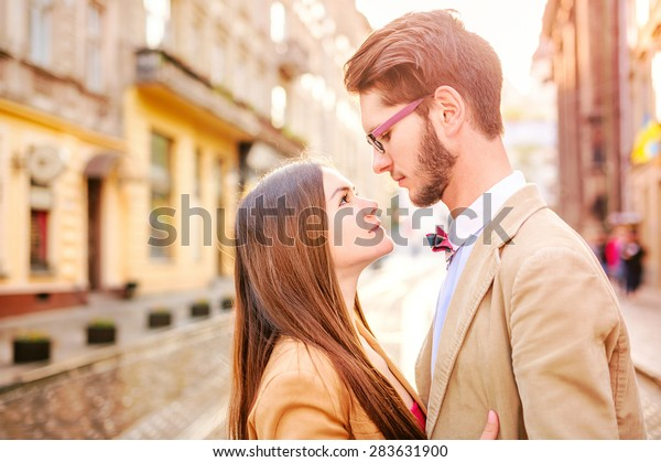 Young fashion elegant stylish couple posing on streets of european city in summer, vintage color sunlight