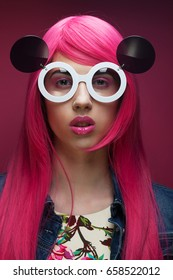 young fashion girl with pink hair and big sunglasses