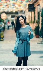 Young fashion girl posing with style wearing a denim jacket stylish draped over her shoulders in a iconic look, over a light cashmere dress. Retro-inspired '80s outfit on the city streets bazaar