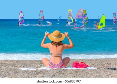 Young fashion girl resting on the beach. Windsurfer in the background