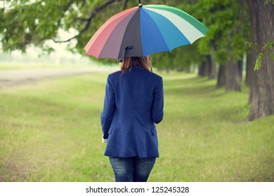 Young fashion girl with umbrella at spring outdoor.
