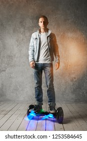 Young fashion guy rides a hoverboard in casual clothes
