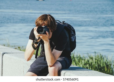 Young fashion hipster man with backpack sitting and photographing river bridge background