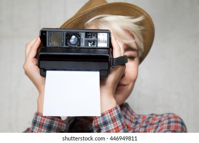 Young fashion hipster smiling girl in a hat with a camera for instant photos