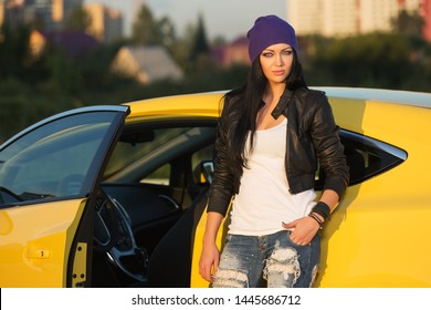Young fashion hipster woman leaning on her car  Stylish female model in black leather jacket purple beanie and ripped jeans
