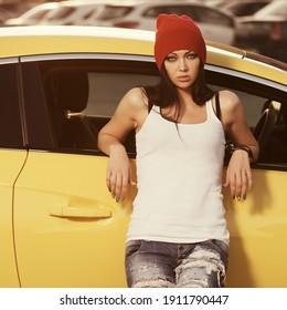 Junge Mode-Hipster-Frau auf ihrem Auto Stilvolles weibliches Modell in weißer Tandemütze und rippelndem Jeans