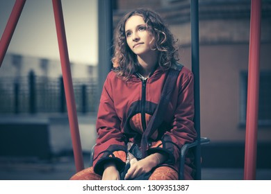 Young fashion hipster woman sitting on the swing  Stylish trendy model with curly hairs in red hoodie sweatshirt
