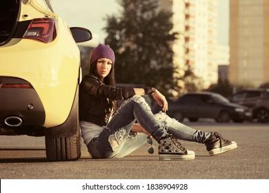 Junge Mode-Hip-Frau sitzt auf Gehsteig und lehnt sich auf Auto Stilweibliches Modell in schwarzem Ledermantel, violetter Mütze und gerippte Jeans