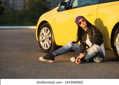 Young fashion hipster woman in sunglasses sitting on sidewalk leaning on car  Stylish female model in black leather jacket purple beanie and ripped jeans