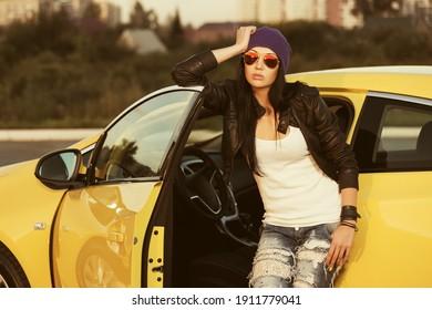 Young Modehipster in Sonnenbrillen auf ihrem Wagen Stilvolles Frauenmodell in schwarzem Lederjacke, violette Mütze und rippte Jeans