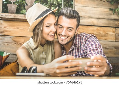 Young fashion lover couple at beginning of love story - Handsome man taking selfie with pretty woman at fashion coffee bar - Relationship concept with nice boyfriend and girlfriend - Warm retro filter