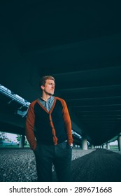 Young fashion man standing under a bridge