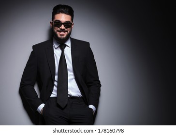 young fashion man wearing sunglasses smiles for the camera while leaning with his back on a wall and standing with his hands in his pockets. on a dark background
