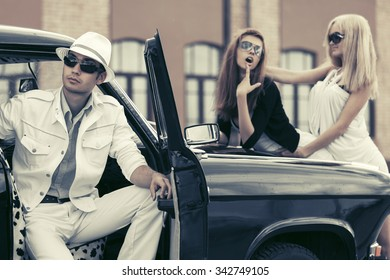 Young fashion man and women by retro car